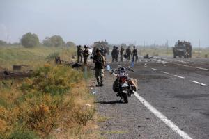 Forensic officers investigate after a roadside bomb killed 14 policemen in Igdir, eastern Turkey, Tuesday, Sept. 8, 2015. Kurdish rebels are suspected of detonating a bomb in the eastern province of Igdir as a police vehicle escorting a group of customs officials to a border gate was passing by, the Anadolu Agency reported. ( IHA Agency via AP ) TURKEY OUT